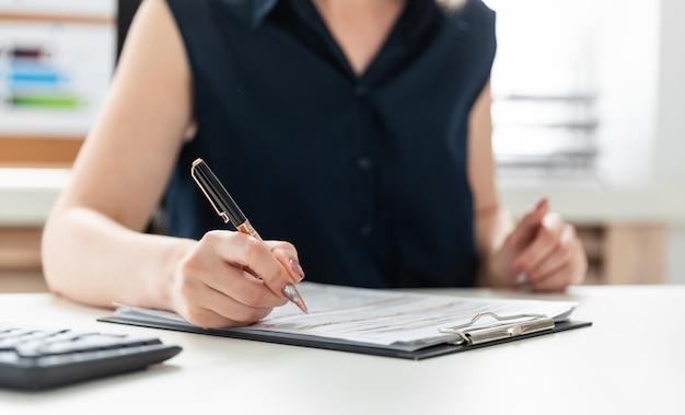 Les mains des femmes remplissent un questionnaire.