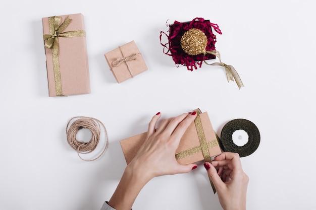 Mains de femmes avec un ruban rouge de manucure noué sur la boîte avec un cadeau