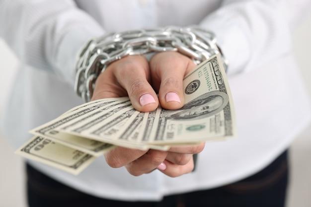 Les mains des femmes sont attachées avec une chaîne et détiennent une dépendance à l'argent en billets de cent dollars américains