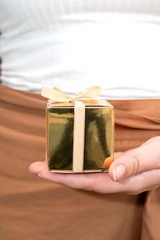 Mains de femmes tenant une boîte cadeau en or, cadeau de vacances, anniversaire, noël, père ou mère, gros plan de la saint-valentin