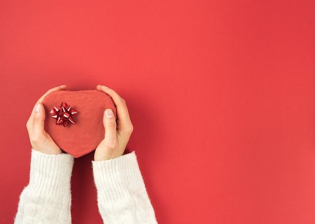 Mains de femmes tenant une boîte en forme de coeur sur fond rouge. saint valentin