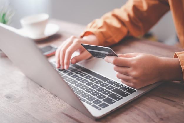 Mains de femmes tenant une carte de crédit et travaillant sur un ordinateur portable paiement en ligne pour les achats en ligne