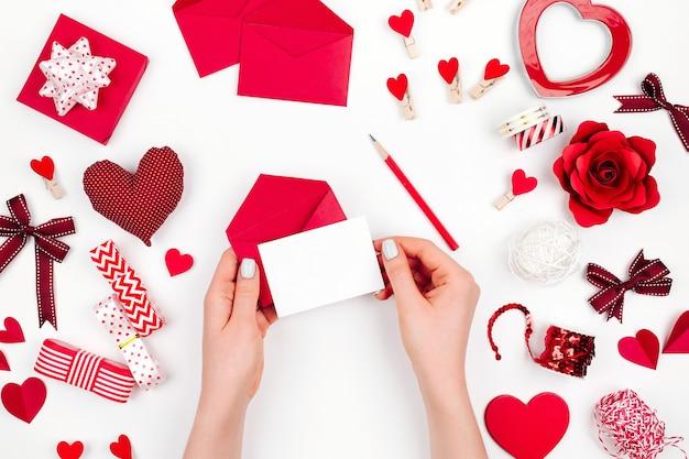 Mains de femmes tenant une carte de saint-valentin sur fond blanc avec une décoration romantique. mise à plat