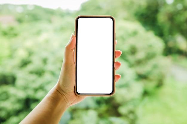 Les mains des femmes tenant l'écran de l'espace de copie vierge de téléphone portable