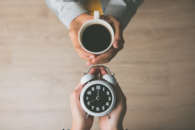 Mains de femmes tenant une tasse de café et réveil