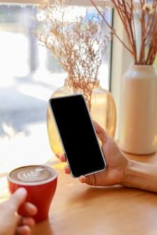 Mains de femmes tenant un téléphone intelligent à écran vide vide dans le café.