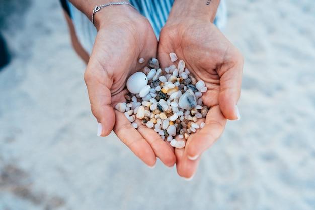Les mains des femmes tiennent beaucoup de petits cailloux