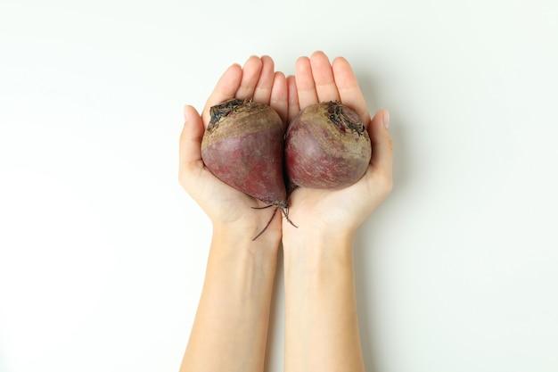 Les mains des femmes tiennent des betteraves fraîches sur fond blanc