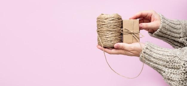 Les mains des femmes tiennent un cadeau et une bobine de corde sur fond rose, gros plan, espace de copie. concept de cadeaux faits à la main. noël, nouvel an, anniversaire, saint-valentin, fond de vacances, bannière.