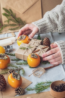 Les mains des femmes tiennent des cadeaux pour le nouvel an. fond de noël avec coffrets cadeaux, cônes, arbre de noël et kaki, vue de dessus, gros plan. cadeau fait main.