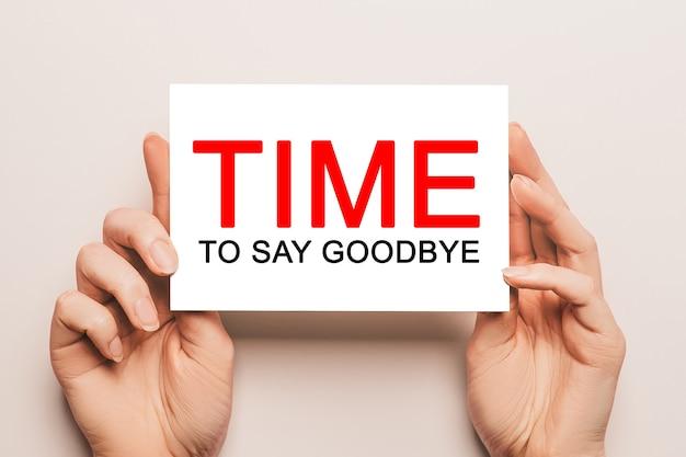 Les mains des femmes tiennent du papier cartonné avec le texte time to say goodbye sur fond jaune. concept commercial et financier