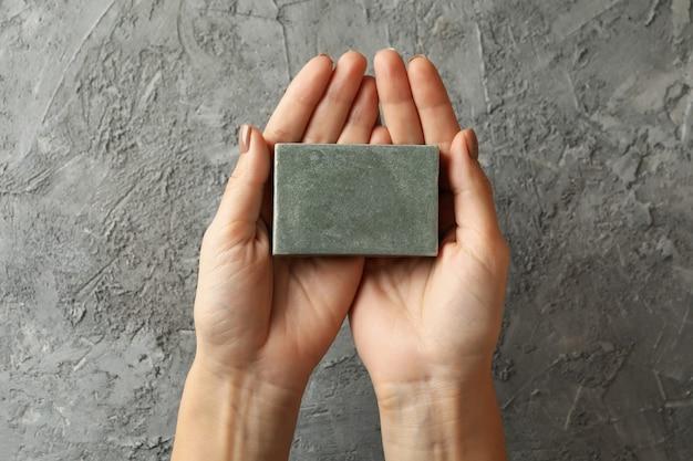 Les mains des femmes tiennent du savon artisanal sur gris