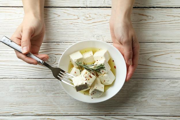 Les mains des femmes tiennent la fourchette et le bol avec du fromage feta sur une surface en bois blanc