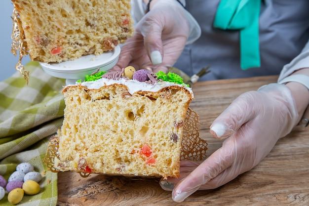 Les mains des femmes tiennent un gâteau de pâques coupé à base de pâte à levure