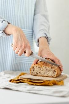 Les mains des femmes tiennent le pain dans le contexte d'un tablier léger