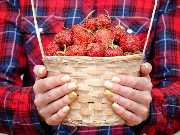 Les mains des femmes tiennent un panier en osier de fraises mûres. fond en bois clair