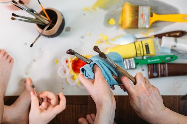 Les mains des femmes tiennent des pinceaux peignant une image sur un chevalet
