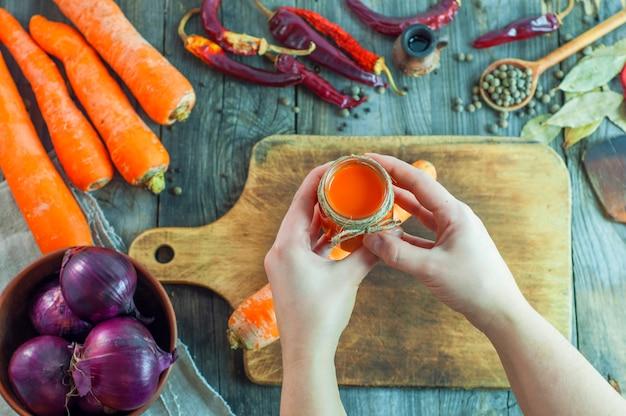 Les mains des femmes tiennent un pot de jus de carotte