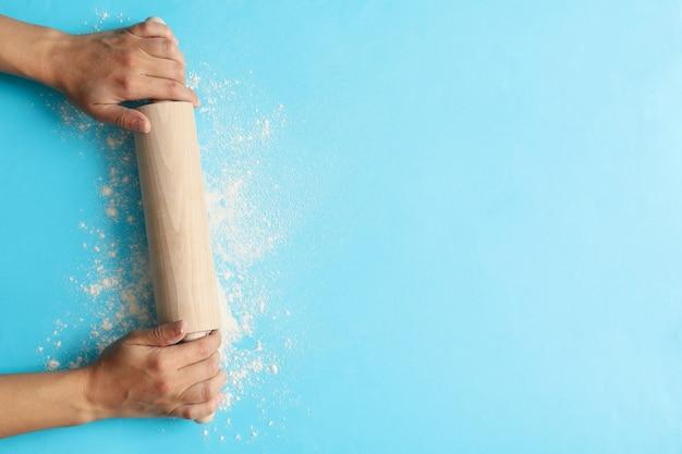 Les mains des femmes tiennent le rouleau à pâtisserie sur fond bleu