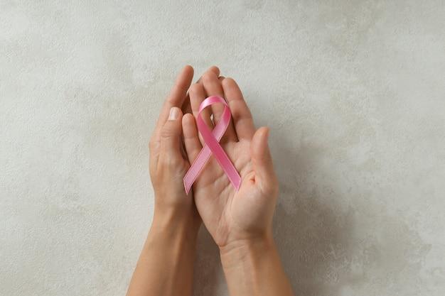 Les mains des femmes tiennent un ruban de sensibilisation au cancer du sein sur un fond texturé blanc