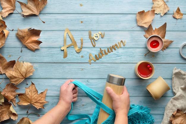 Les mains des femmes tiennent un sac en filet écologique et une fiole thermos en bambou. thé zéro déchet en automne, texte a pour l'automne.