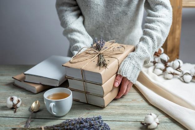 Les mains des femmes tiennent soigneusement une pile de livres dans des couvertures en papier kraft enveloppées de corde et décorées de lavande