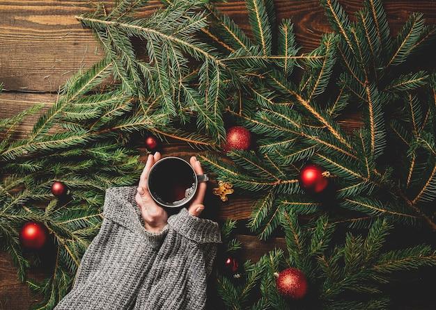 Les mains des femmes tiennent une tasse de thé avec arbre de noël sur une table