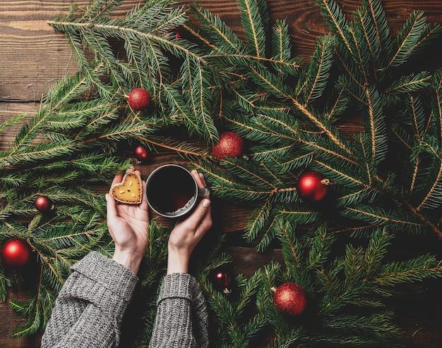 Les mains des femmes tiennent une tasse de thé et de biscuits avec arbre de noël sur une table