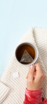 Les mains des femmes tiennent une tasse de thé chaud le matin sur le fond d'un plaid tricoté blanc jeune w...