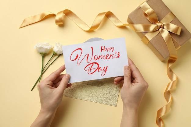 Les mains des femmes tiennent le texte happy women's day sur fond beige avec des roses, une enveloppe et une boîte cadeau