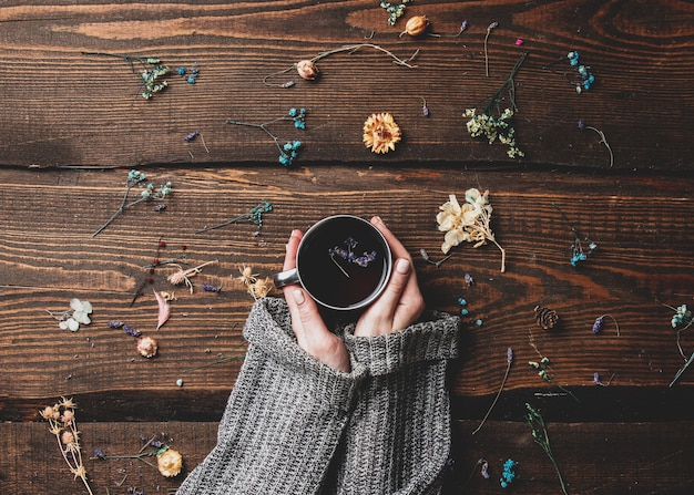 Les mains des femmes tiennent le thé à côté de brindilles séchées sur une table en bois