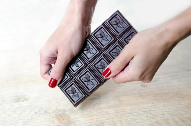 Les mains des femmes tiennent toute une barre de chocolat.