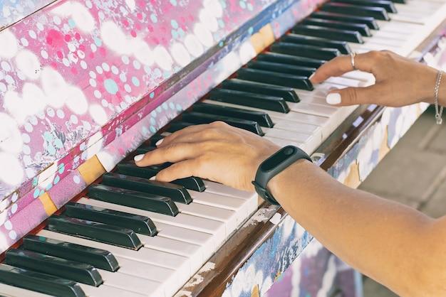 Les mains des femmes sur les touches du vieux piano