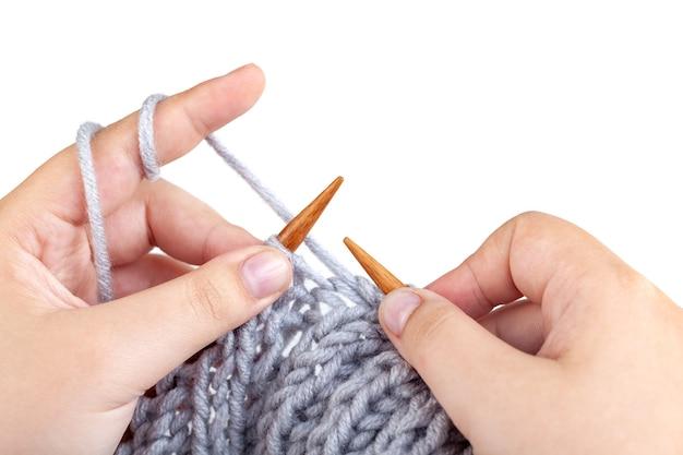 Mains de femmes tricotées en laine grise