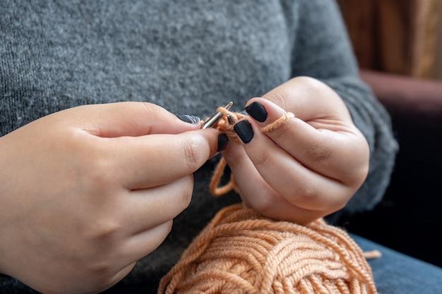 Les mains des femmes tricotent de la laine colorée. tricot à la main