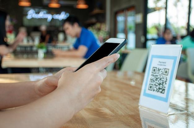 Les mains des femmes utilisent le téléphone pour scanner le code qr pour sélectionner le menu alimentaire. scannez pour obtenir des réductions ou payer pour de la nourriture. le concept d'utiliser un téléphone pour transférer de l'argent ou payer de l'argent en ligne sans espèces.