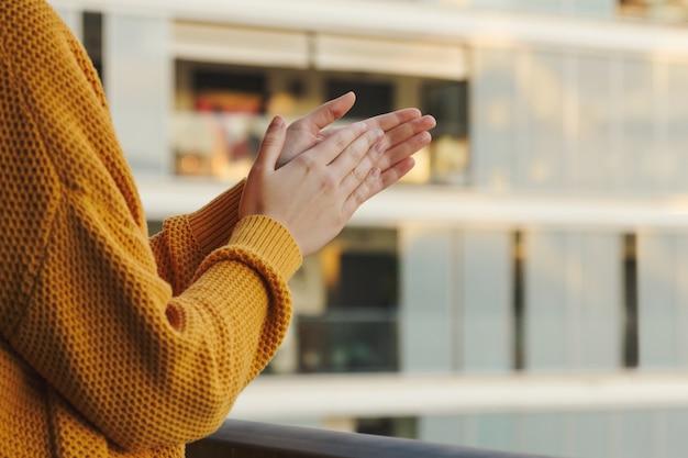 Les mains d'une fille applaudissant depuis son balcon pour soutenir ceux qui combattent le coronavirus