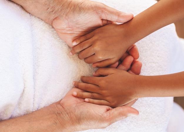 Mains de fille asiatique enfant tenant mains de grands-parents âgés peau ridée avec soin et amour