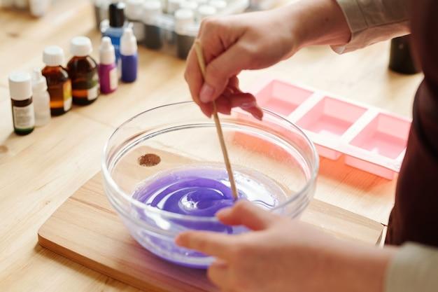 Mains de fille créative mélangeant la couleur lavande avec une masse de savon liquide dans de la verrerie avant de la verser dans des moules en silicone