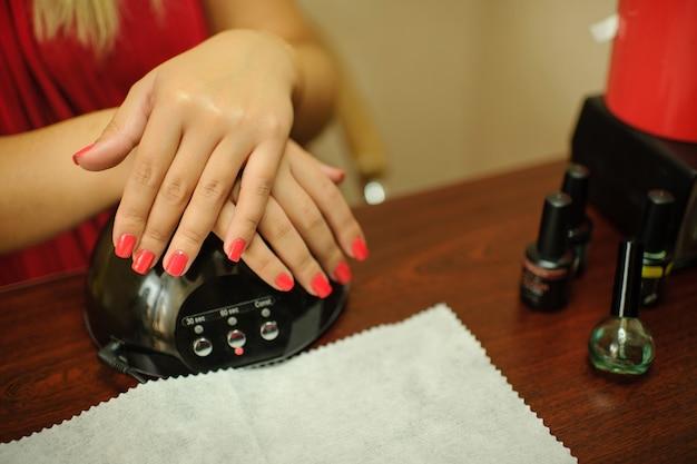 Mains d'une fille avec une manucure douce sur une machine pour le séchage uv. soin des ongles après peinture.