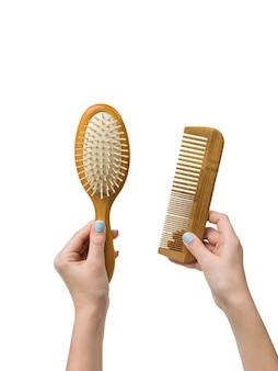 Les mains d'une fille avec des peignes en bois isolés sur fond blanc. outils pour le soin des cheveux.