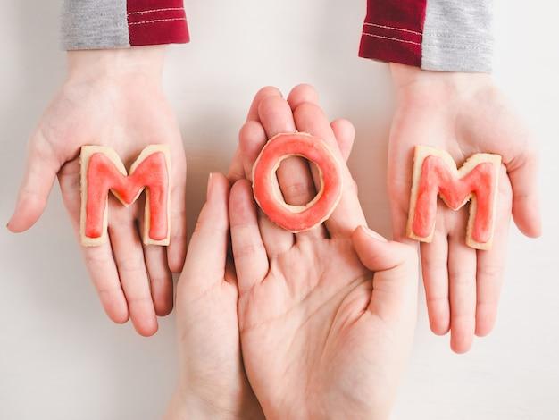 Mains d'une fille plus jeune et de sa mère
