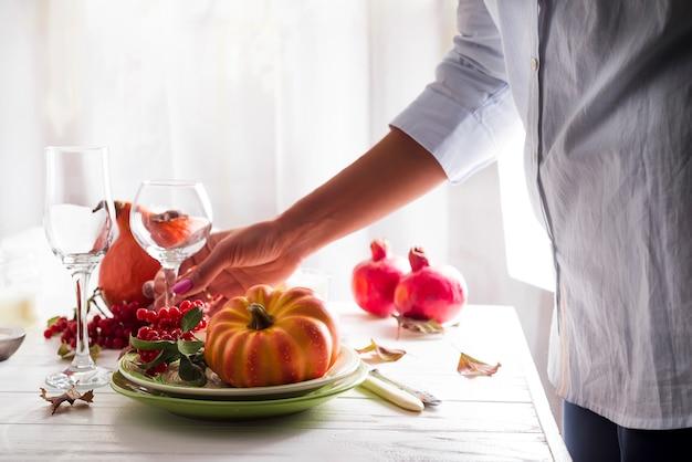 Les mains de la fille préparent la table de fête de thanksgiving