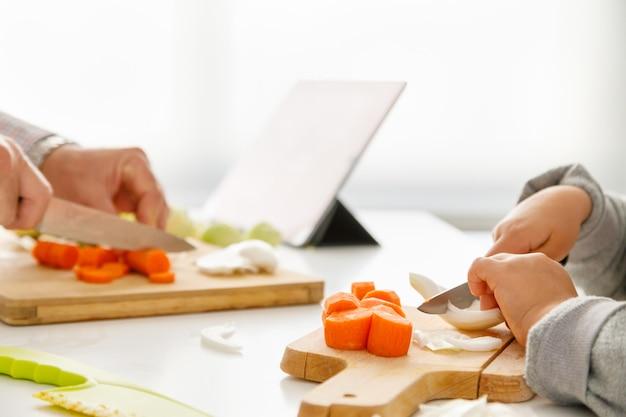 Les mains d'une fille et son père préparent des aliments dans la cuisine avec une tablette en arrière-plan