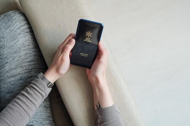Mains de fille avec téléphone portable assis sur le canapé et en attente de profil de chargement de consultation médicale en ligne