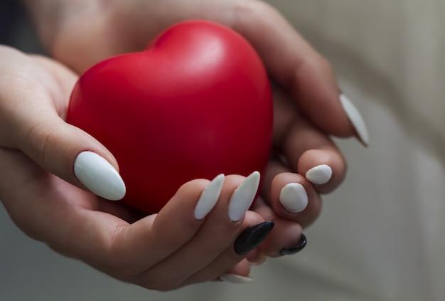 Mains de la fille tenant coeur rouge