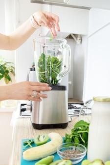 Les mains des filles préparent un smoothie vert, mettent des feuilles d'épinards fraîches dans un mélangeur. concept d'alimentation saine. végétarisme, alimentation végétalienne, alimentation fitness, détox, préservation de la jeunesse.