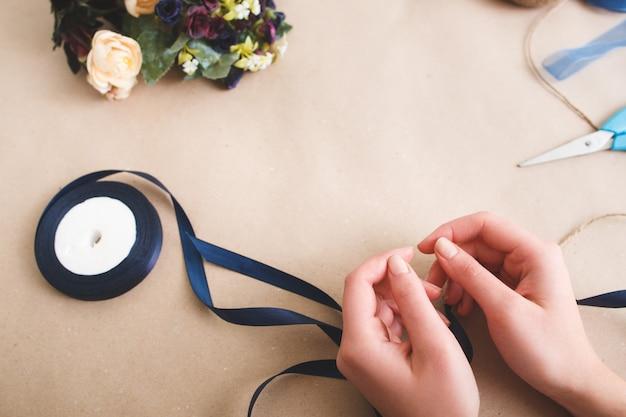 Mains avec des fleurs artificielles colorées et des rubans sur une surface beige