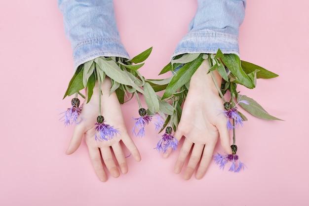 Les mains et les fleurs printanières sont sur un soin de table rose. cosmétiques nature