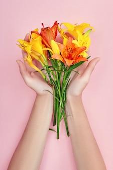 Les mains et les fleurs printanières sont sur une table rose